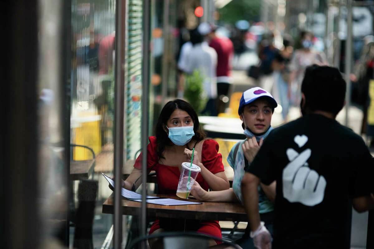 FILE. Customers wearing protective masks order food outside a restaurant in New York City. (Photo by Jeenah Moon/Getty Images)