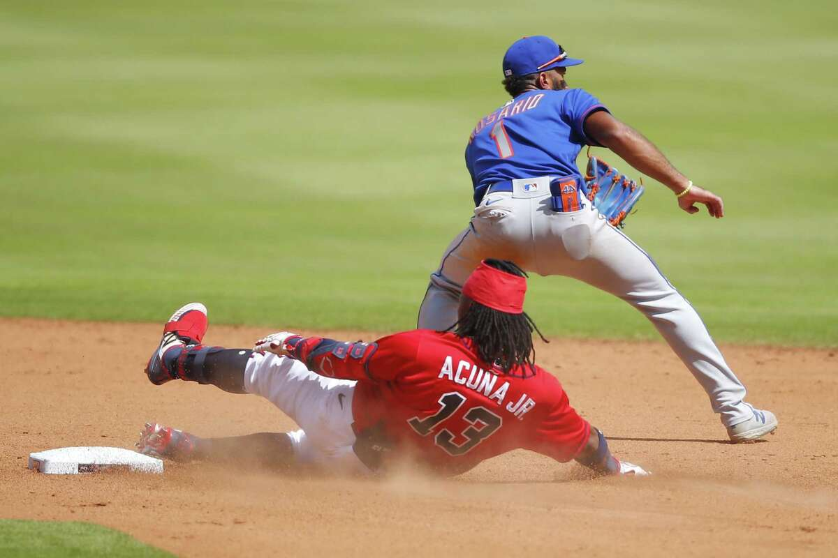 ATLANTA, GA - AUGUST 02: Ronald Acuna Jr. #13 of the Atlanta Braves slides into second base after hitting a double as Amed Rosario #1 of the New York Mets awaits the ball in the eighth inning of an MLB game at Truist Park on August 2, 2020 in Atlanta, Georgia. (Photo by Todd Kirkland/Getty Images)
