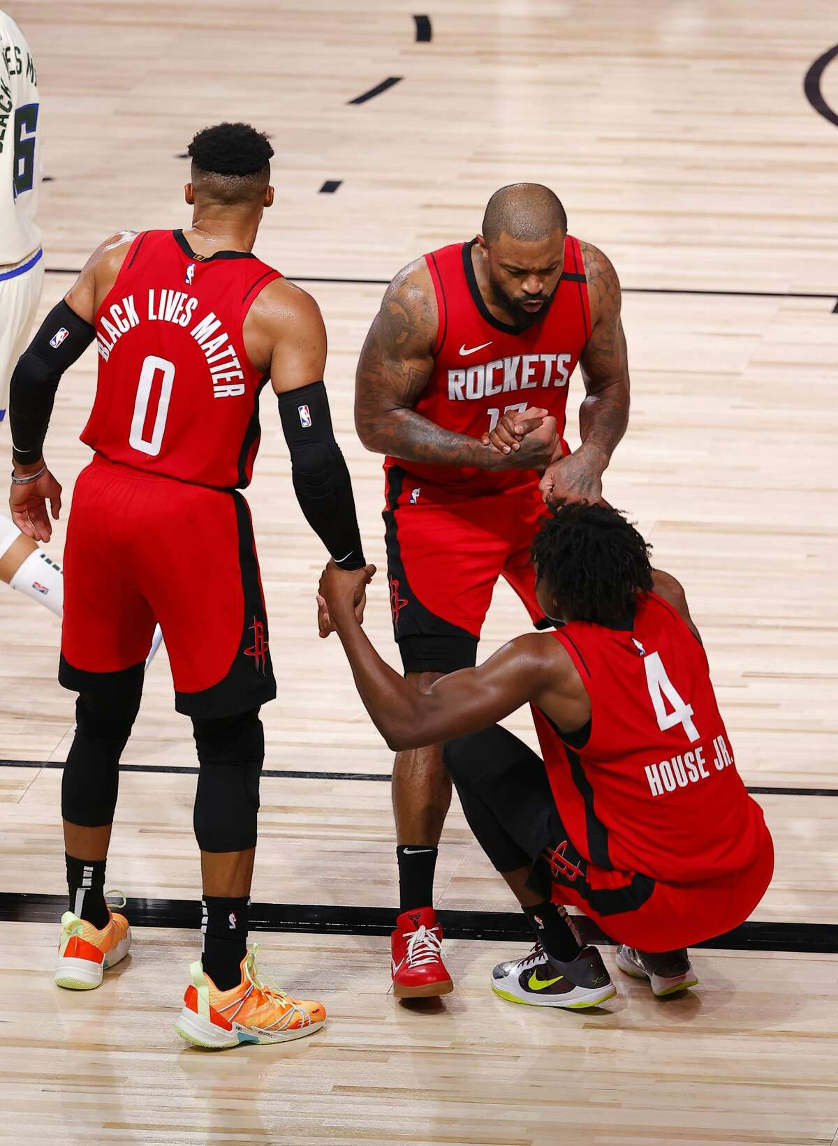 Houston Rockets' Danuel House Jr. (4) is helped up by teammates Russell Westbrook, left, and P.J. Tucker during the team's NBA basketball game against the Milwaukee Bucks on Sunday, Aug. 2, 2020, in Lake Buena Vista, Fla. (Mike Ehrmann/Pool Photo via AP)