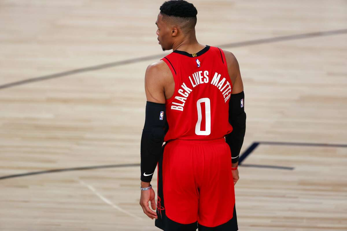 """Houston Rockets' Russell Westbrook wears """"Black Lives Matter"""" on the back of his jersey during the team's NBA basketball game against the Milwaukee Bucks on Sunday, Aug. 2, 2020, in Lake Buena Vista, Fla. (Mike Ehrmann/Pool Photo via AP)"""