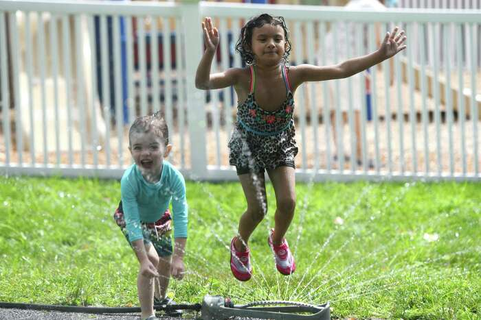 Theodore Veri, 3, and Johanna Molina, 5, play in the sprinklers during outdoor play time at Children's Learning Centers in Stamford, Conn. Thursday, July 30, 2020. The child care business re-opened roughly a month ago at half capacity and with many restrictions.