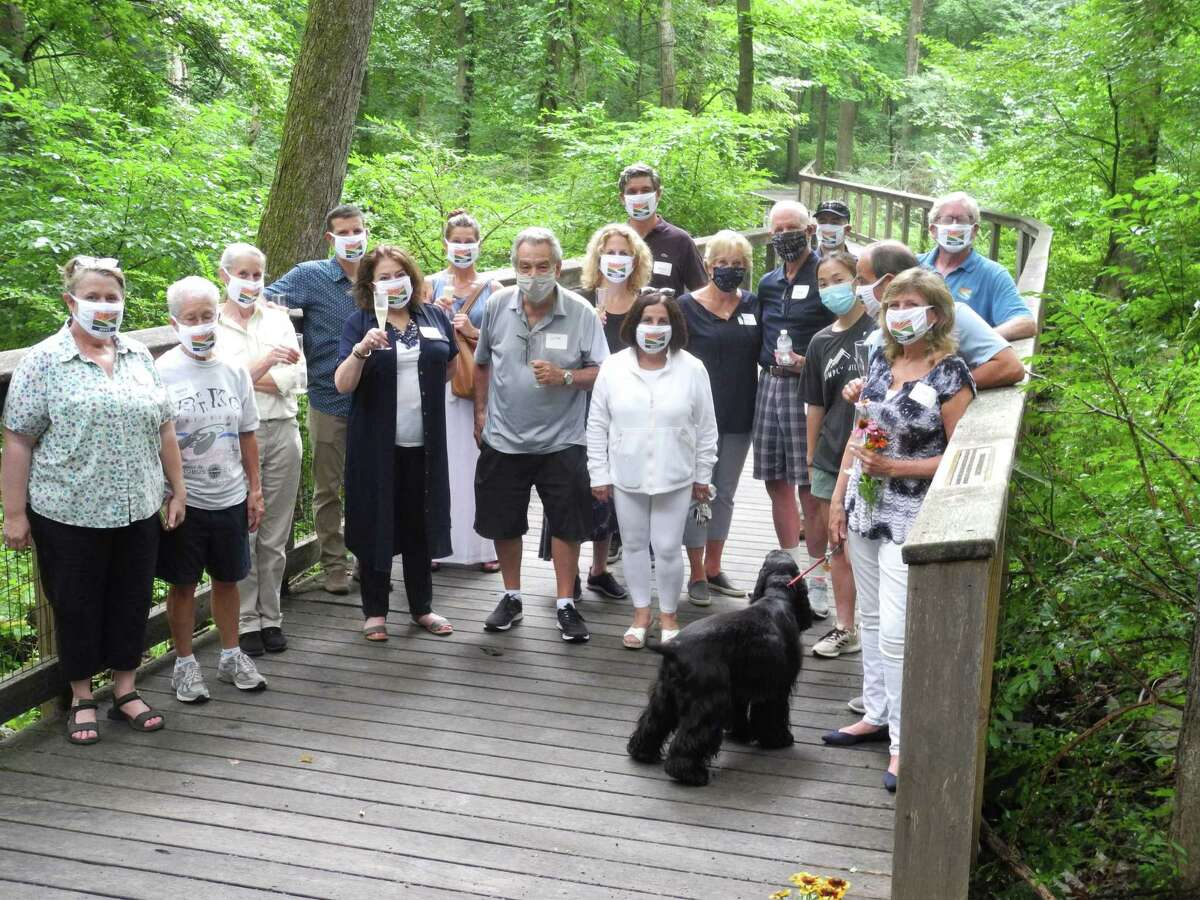 A group of well wishers joins Pat Sesto, at right, at a celebration honoring her on July 30. The boardwalk on which they stand has been named for her. Rendell-Baker recalled how just three years ago she, Sesto, and other early trail advocates brought potential donors to the woods where it was still rough and swampy.