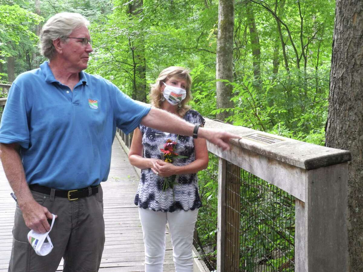 Norwalk River Valley Trail president Charlie Taney points to the plaque dedicated for the Patricia Sesto Boardwalk on July 30, 2020 in Wilton, CT. Sesto, right, has spearheaded the trail's progress for more than a decade.