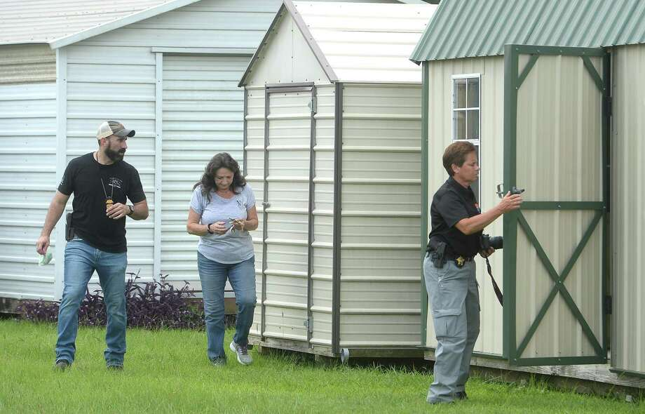 Sandra Daughtry provides access to nearby sheds as members of the DEA, ATF, and other law enforcement agencies investigate during a raid at Jake's Fireworks Super Store and surrounding warehouses Wednesday in Nederland. Several employees were detained inside as the raid continued before eventually being released. One man was handcuffed and taken into custody. Photo taken Wednesday, July 15, 2020 Kim Brent/The Enterprise Photo: Kim Brent / The Enterprise / BEN