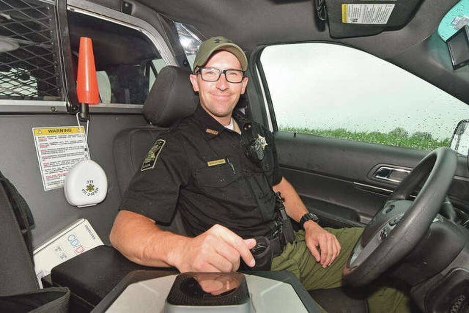 Cass County Sheriff's Deputy Brian McCombs sits at the wheel of his squad car.