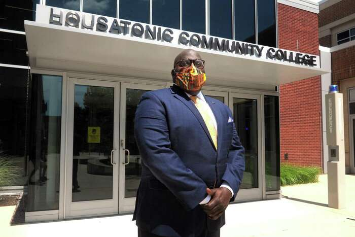 New CEO Dwayne Smith poses near an entrance to Housatonic Community College, in Bridgeport, Conn. July 28, 2020.
