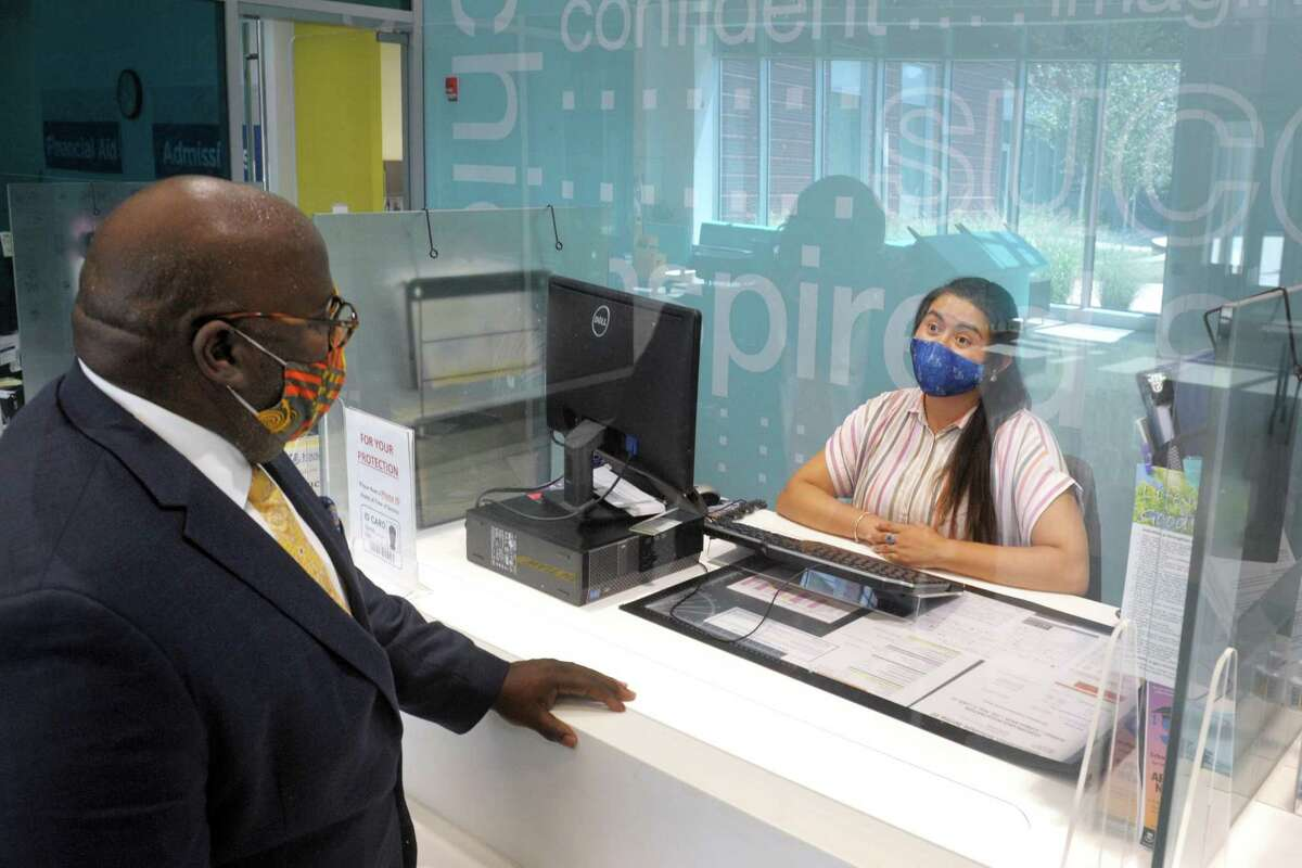 New CEO Dwayne Smith speaks with staff member Gloria Suarez at the welcome desk of Housatonic Community College, in Bridgeport, Conn. July 28, 2020.