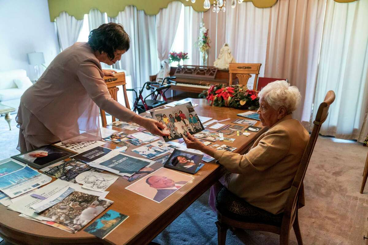 FAnita Arnold, left, works with her mother, Juanita Davis, at the dining room table in Forest Park, Okla., where Juanita has been assembling the photo book for their family reunion next month.