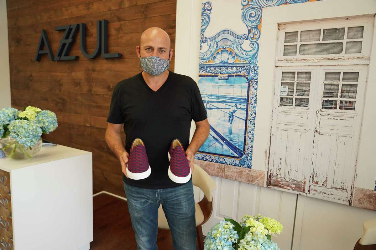 Manuel Rodrigues holds a pair of his shoes that were handmade in Portugal as he stands in his new store in New Canaan, the third new business to open in July in the town. Rodrigues, the owner, recently opened, and posed for this picture.