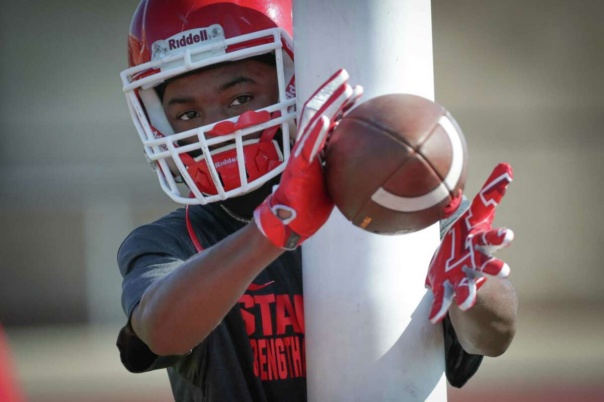 Stafford High School freshman Chris Holland catches passes during the first day of high school football practice, which is only taking place at a select number of schools in the Houston area Monday, Aug. 3, 2020, in Stafford.