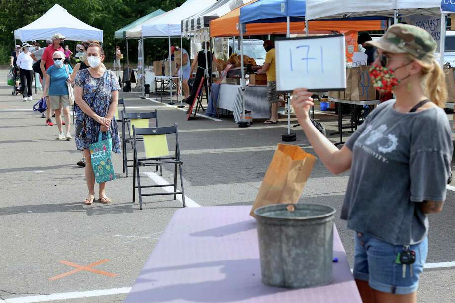 Rachel Naumann of Norwalk-based Wave Hill Breads holds up an order number at the Westport Farmer's Market on Thursday, July 30, 2020, in Westport, Conn. Photo: Jarret Liotta / Jarret Liotta / ©Jarret Liotta 2020