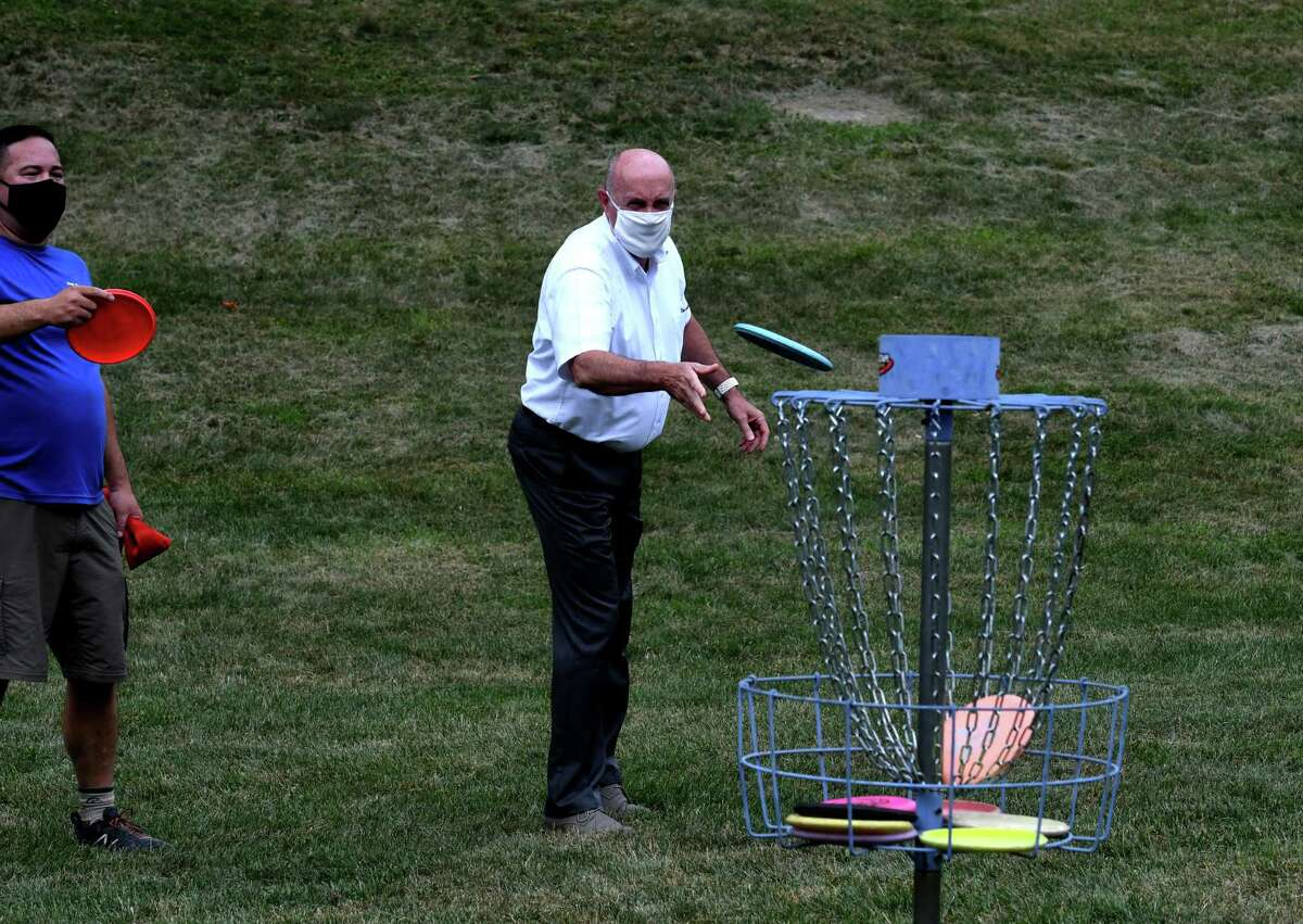 Troy Mayor Patrick Madden tries his hand at disc golf during the opening of a new nine-hole course in Prospect Park on Monday Aug. 3, 2020, in Troy, N.Y. Disc golf is played much like golf. However, instead of a ball and clubs, players use a flying disc or Frisbee with the objective of completing each hole in the fewest throws. (Will Waldron/Times Union)