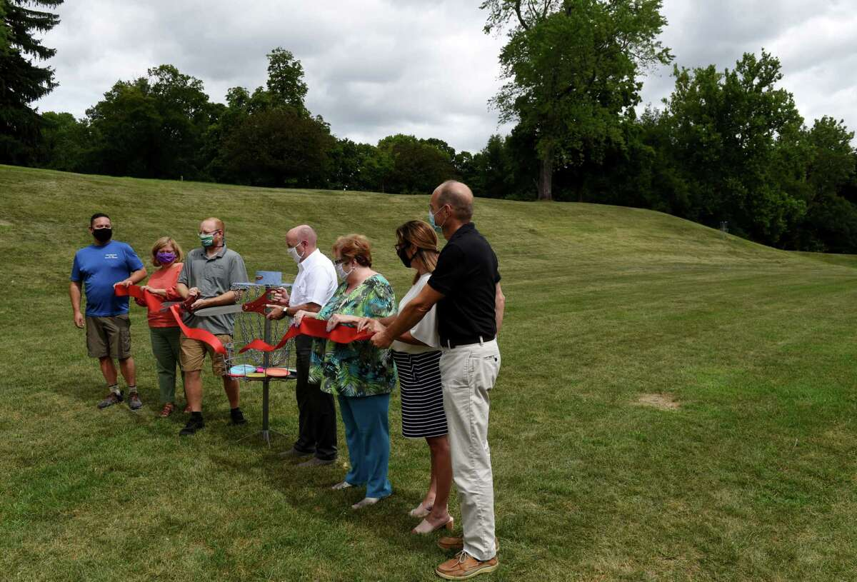 A ribbon is cut to mark the opening of Troy's new nine-hole disc golf course in Prospect Park on Monday Aug. 3, 2020, in Troy, N.Y. Disc golf is played much like golf. However, instead of a ball and clubs, players use a flying disc or Frisbee with the objective of completing each hole in the fewest throws. (Will Waldron/Times Union)