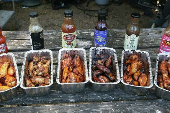An assortment of chicken wings used with the following sauces (left to right): Frank's RedHot Original, Black Garlic Wing Sauce, Rodeo Wing Sauce, Golden Hog Huckleberry Heat, Smokey Plum Chipotle Sauce and Watermelon Grill & Glaze.