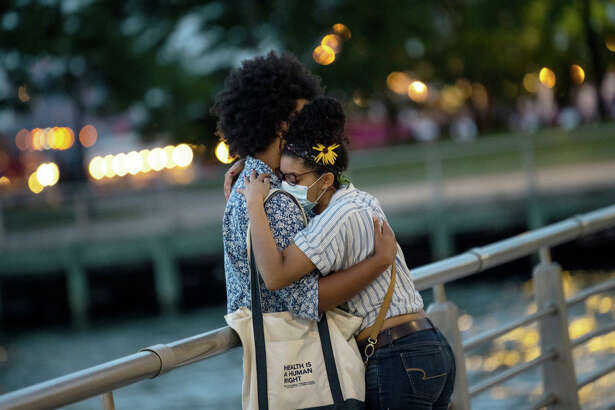 NEW YORK, NEW YORK - AUGUST 01: A couple wearing masks is seen embracing along the Hudson River Greenway near Chelsea Piers as the city continues Phase 4 of re-opening following restrictions imposed to slow the spread of coronavirus on August 01, 2020 in New York City. The fourth phase allows outdoor arts and entertainment, sporting events without fans and media production. (Photo by Alexi Rosenfeld/Getty Images)