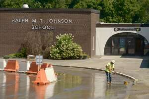 A worker clears away dirt from the driveway of Ralph M.T. Johnson School on Friday afternoon. Renovation work will continue at Johnson and Rockwell schools thru the school year. Friday,August 30, 2019, in Bethel, Conn.
