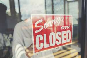 Store owner putting up a closed sign in the window. Sign says: sorry were closed