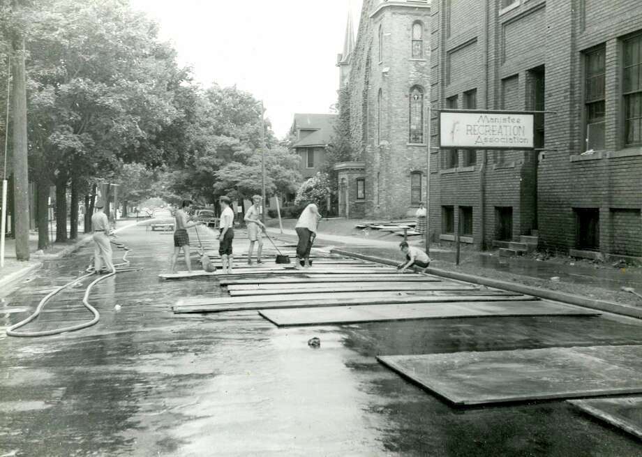 Cleaning the scenery boards of the Manistee Summer Theatre on First Street in 1955. (Manistee County Historical Museum photo)