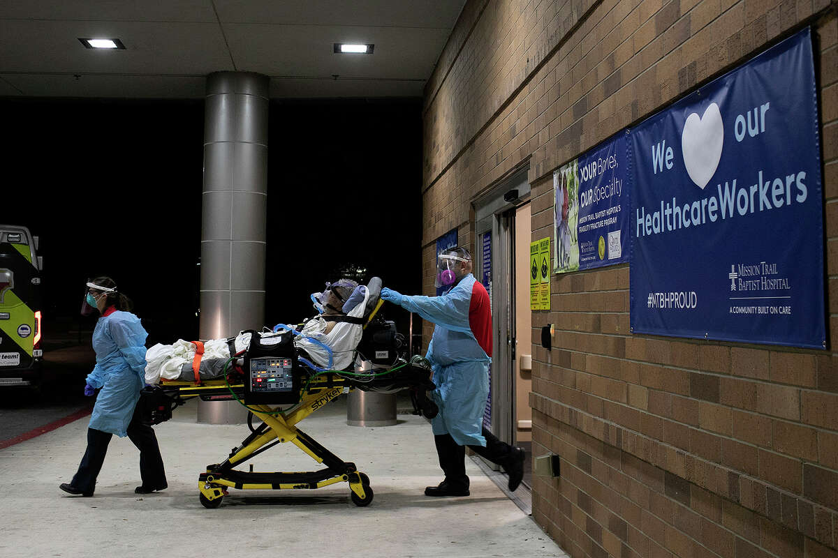 Superior Mobile Health EMT Dominique Sharp and George Lombardo take a COVID-19 positive patient out of a hospital to transfer to home hospice care on July 14, 2020 in San Antonio.