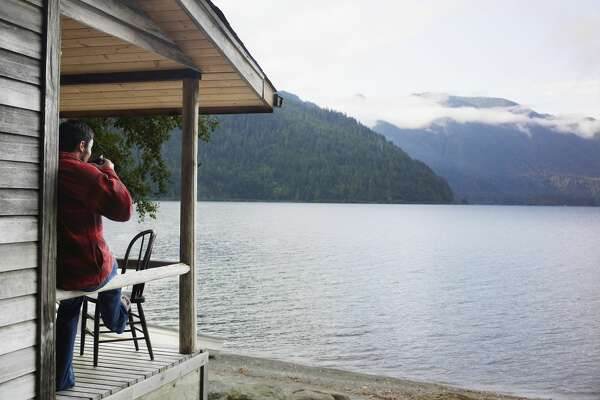 Man drinking coffee on front porch of lake cabin