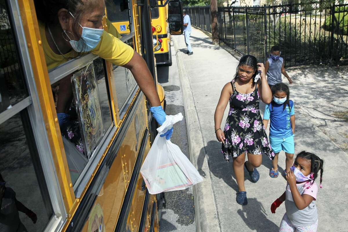 Oralia Santos hands out bags of of reading material as the SAISD Foundation gives away books from a school bus parked at the Rosemont Apartments on Rigsby to local residents on July 28, 2020.