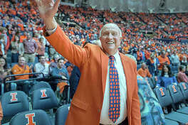In this Dec. 2, 2015 photo, former University of Illinois basketball coach Lou Henson acknowledges the crowd while taking his seat courtside during the dedication of the court in his name at the State Farm Center in Champaign. Henson, the basketball coach who led Illinois back into the national spotlight, died July 25 at age 88.