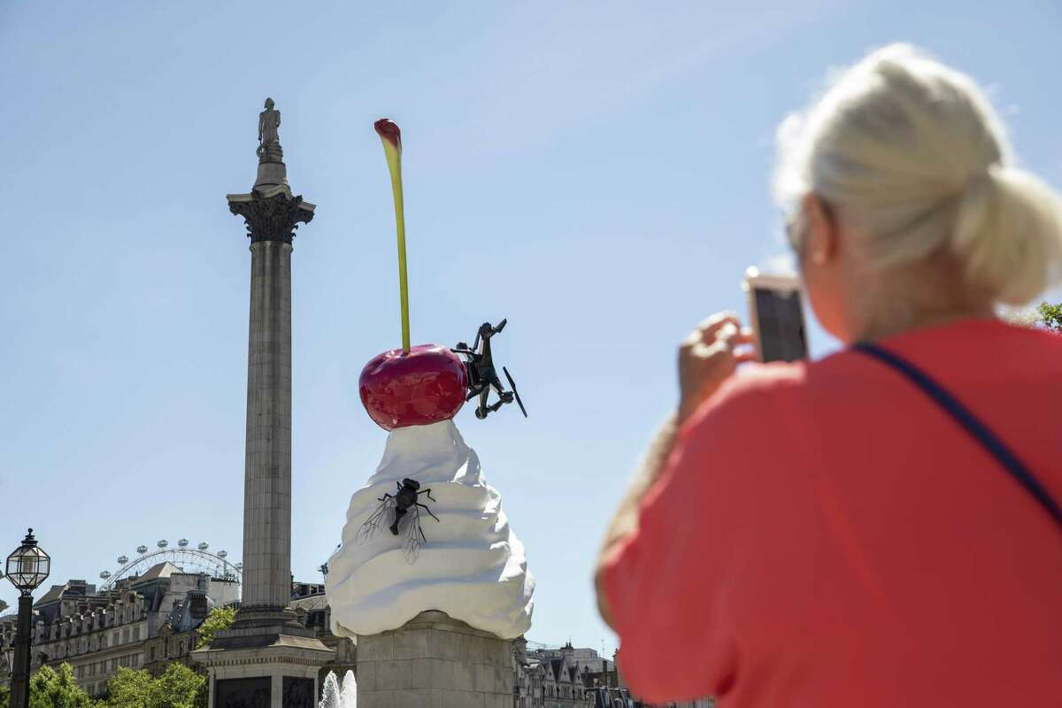 LONDON, ENGLAND - JULY 30: A member of the public takles a photograph of the new addition to the Forth Plinth, entitled 'The End' by British artist Heather Phillipson in Trafalgar Sq on July 30, 2020 in London, England. The sculpture depicts a whirl of cream topped with parasites and a Drone that films passers who can view the footage online. (Photo by Dan Kitwood/Getty Images)