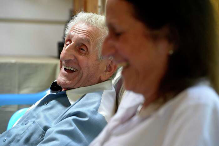 Angelo Testanero, a local musician and arranger who will turn 100 on August 5th, shares a laugh with his daughter Diane Fenwick as he tells a story about burning down a chicken coop when he was young.. Friday, July 31, 2020, in Danbury, Conn.