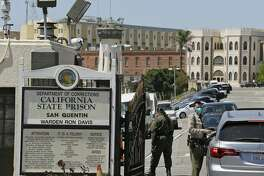 FILE - In this July 9, 2020, file photo, a correctional officer checks a car entering the main gate of San Quentin State Prison in San Quentin, Calif. Two more inmates at San Quentin State Prison near San Francisco died from what appear to be complications of the coronavirus, corrections officials said Monday, Aug. 3, 2020. Two inmates, including a death row inmate, died Sunday at outside hospitals, the California Department of Corrections and Rehabilitation said. (AP Photo/Eric Risberg, File)