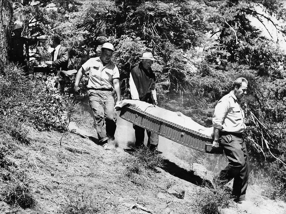 Stephanie Bryan's body, wrapped in canvas is brought down the steep hillside from its crude grave in Trinity County by the coroner and deputy sheriffs. The photo was taken on July 22, 1955.