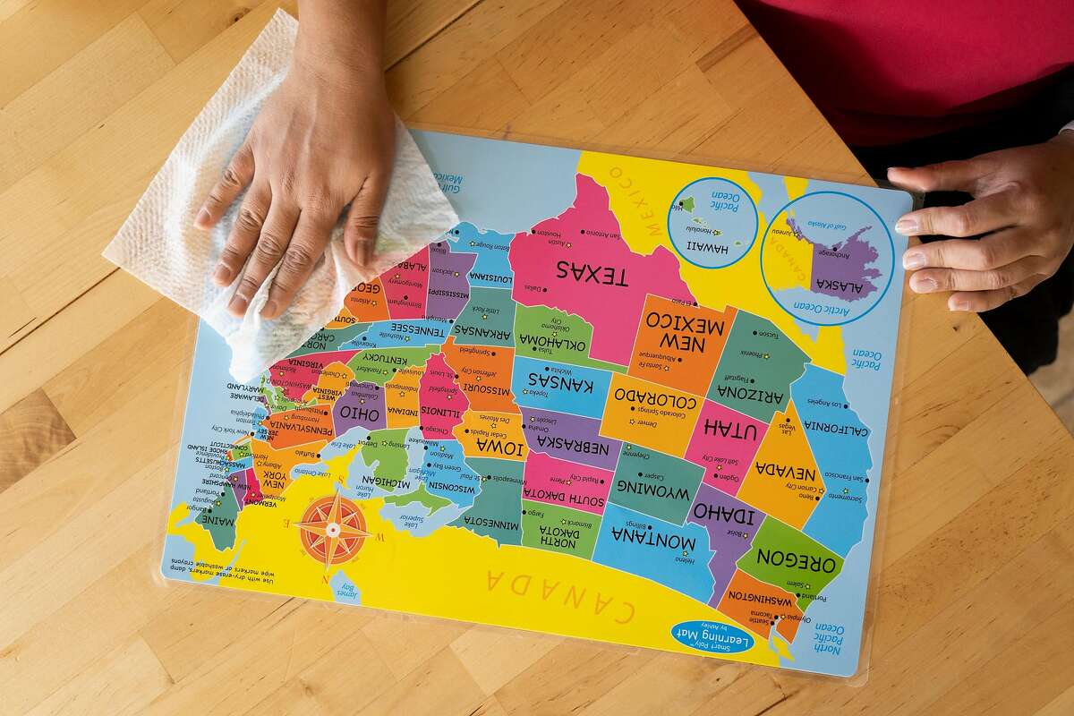 University of Houston professor Sujata Sirsatmakes wipes a kids map of the US with disinfecting wipes in her house on Friday March 6, 2020 in Sugar Land, Texas.
