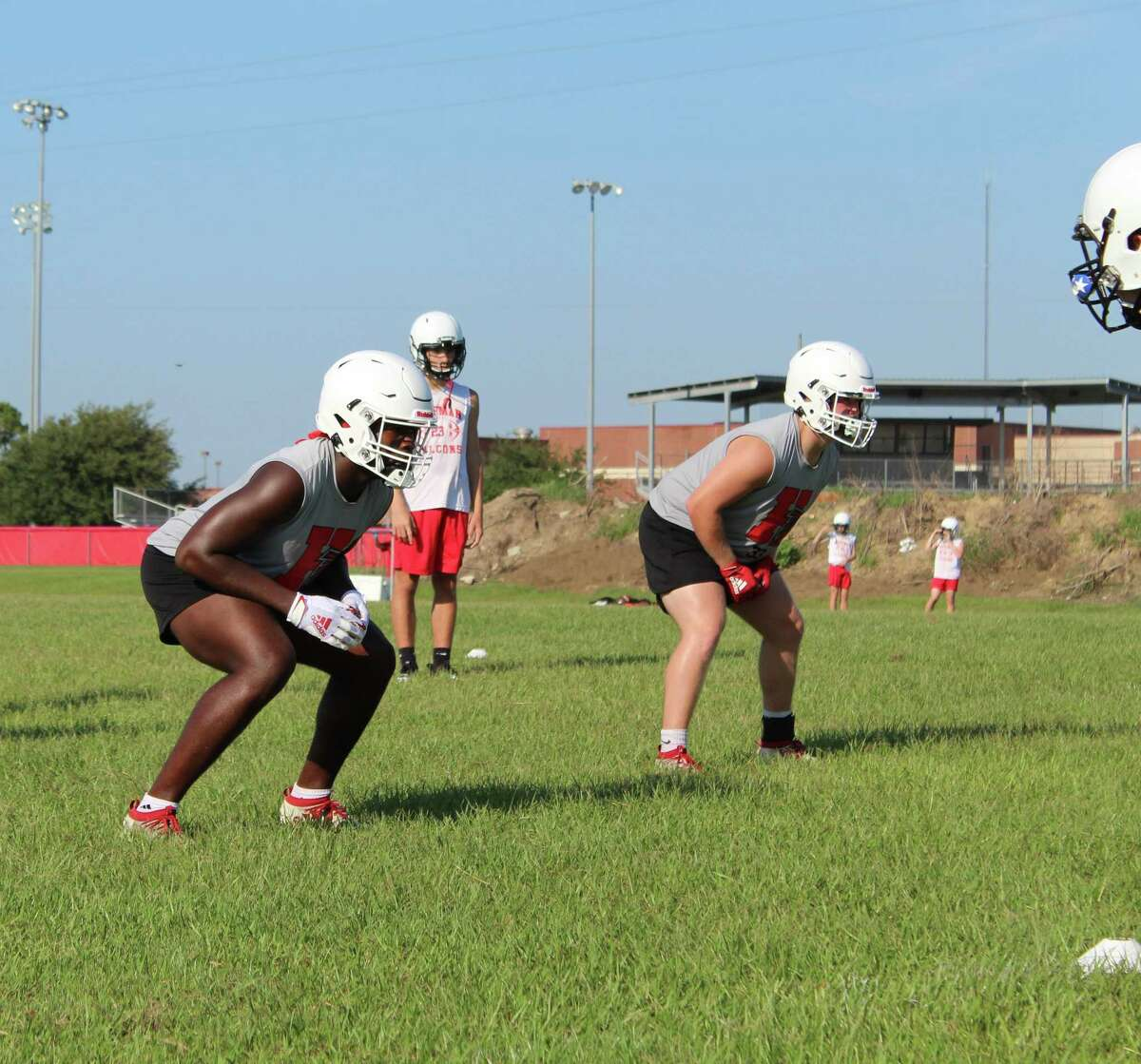 Huffman linebacker Caleb Pierson (left) get ready for a drill on the first day of fall camp