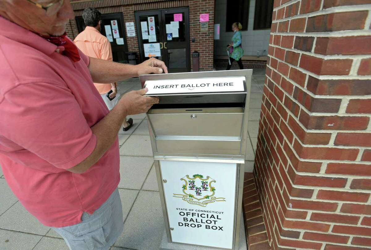 Town Clerk Rick McQuaid surveys the ballot box in front of City Hall on July 21, 2020, in Norwalk, Conn. McQuaid recommends residents place their absentee ballots at the box here or in front of the police station for the Aug. 11, 2020 primary.