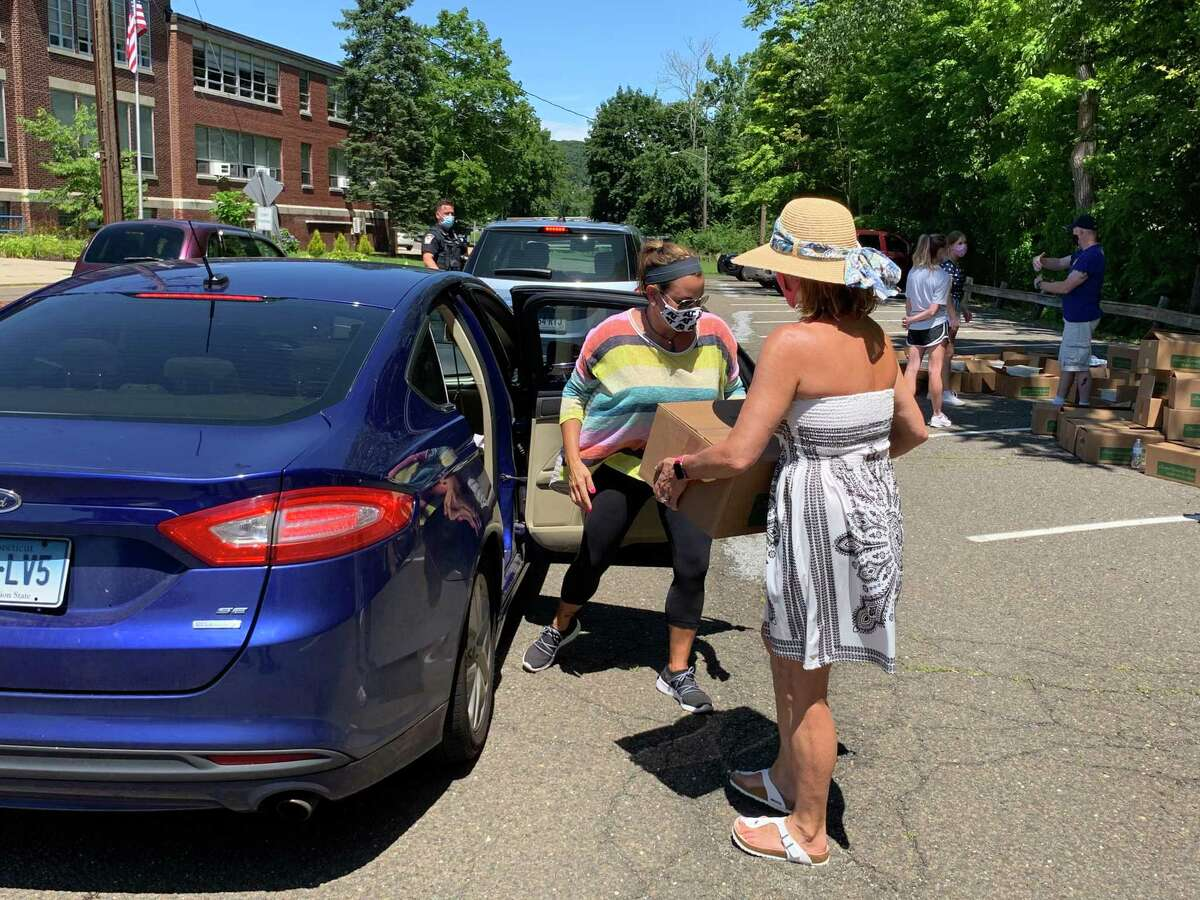 State Reps. Themis Klarides, R-Derby front and her sister, Nicole Klarides-Ditria, R-Seymour, load boxes of fresh fruits and vegetables into a car during the food giveaway at the Seymour Community Center Monday
