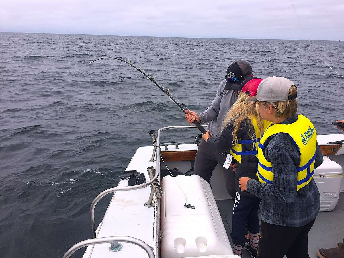 Dad Jacob Walding helps daughter Lana at the rod, while son Ryder waits his turn, fighting a giant Pacific bluefin tuna