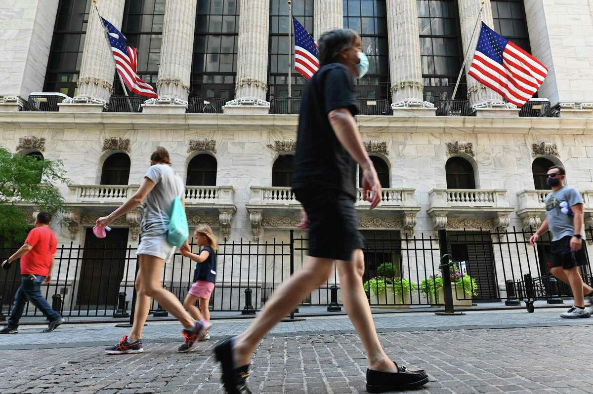 People pass by The New York Stock Exchange (NYSE) on August 3, 2020 at Wall Street in New York City. - Stock markets rose on both sides of the Atlantic August 3, 2020 as hopeful economic data prompted bargain hunting, with some of Asia's equities markets also making solid gains. (Photo by Angela Weiss / AFP) (Photo by ANGELA WEISS/AFP via Getty Images)