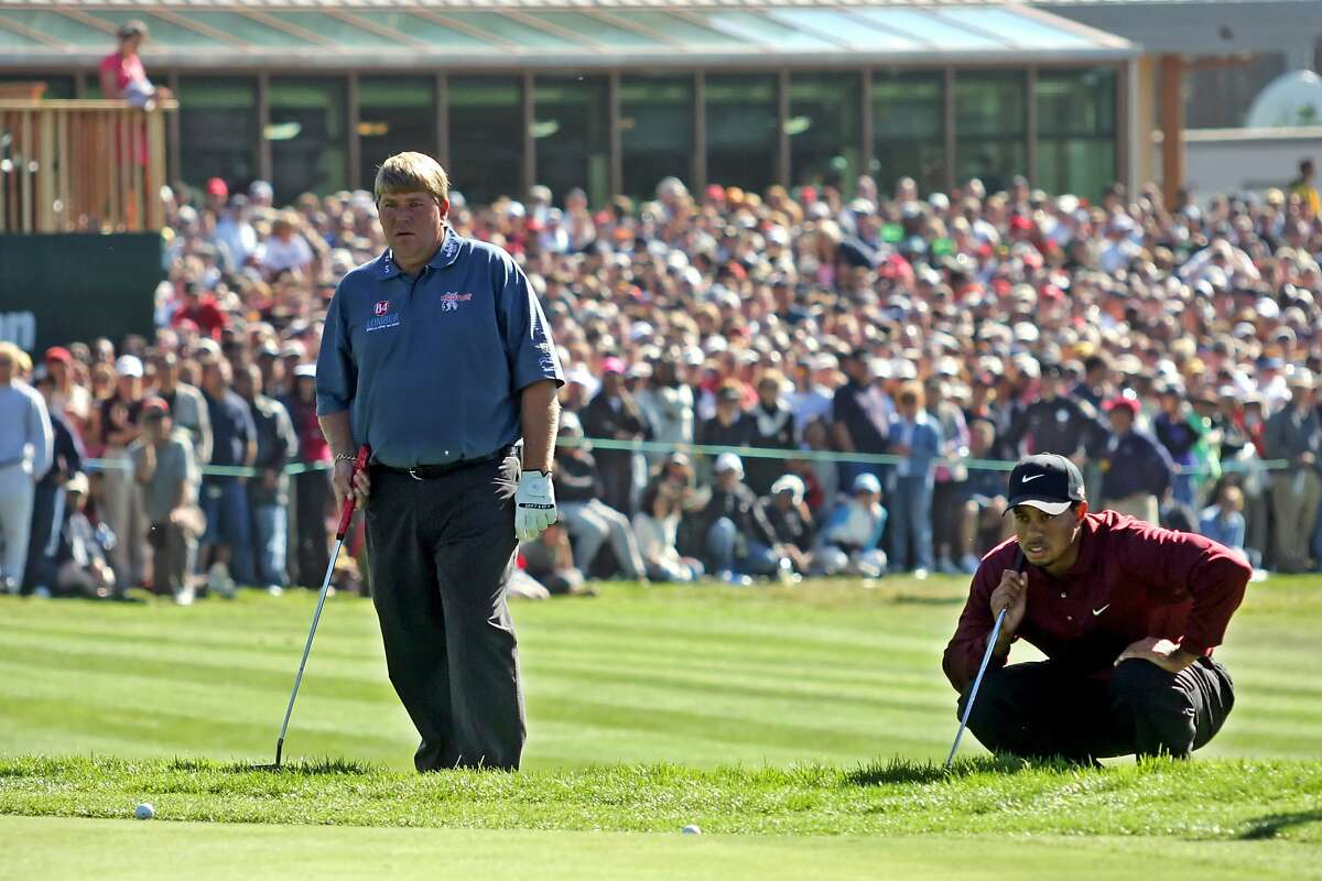 FILE - In this Oct. 9, 2005, file photo, John Daly and Tiger Woods assess their ball positions at No. 18, the first hole of a sudden death playoff, during the final round of the American Express World Golf Championships at Harding Park in San Francisco. On the second playoff hole, Daly had a 15-foot birdie putt to win. He missed, and then he missed the 3-foot par putt. Woods won his 10th World Golf Championship and widened his gap at No. 1 in the world. (AP Photo/Jeff Chiu)