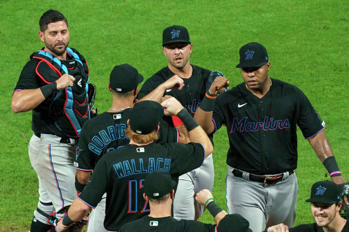 FILE - In this Friday, July 24, 2020, file photo, Miami Marlins' Jesus Aguilar, right, celebrates a win with teammates following a baseball game against the Philadelphia Phillies in Philadelphia. Marlins CEO Derek Jeter blames the teama€™s coronavirus outbreak on a collective false sense of security that made players lax about social distancing and wearing masks. Infected were 21 members of the teama€™s traveling party, including at least 18 players. (AP Photo/Chris Szagola, File)