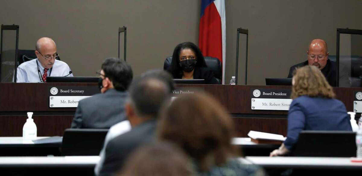 Humble ISD Board Vice President Martina Lemond Dixon, wears her mask, while board president Robert Sitton, right, and board member Robert Scarfo, left, do not wear their masks, due to the partitions between them during the Humble ISD board meeting to discuss the reopening of schools, Monday, August 3, 2020, in Humble.