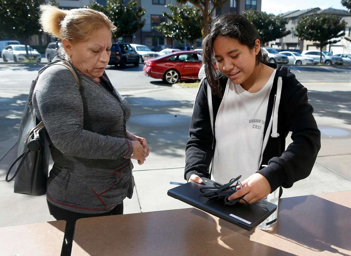 Martha Sanchez (right), a sixth grader at Burbank Elementary School, picks up a Chromebook with her mother Maria Andrade in Hayward, Calif. on Wednesday, March 25, 2020. About 150 of the laptops were made available for students to participate in their school studies while sheltering at home during the coronavirus pandemic.