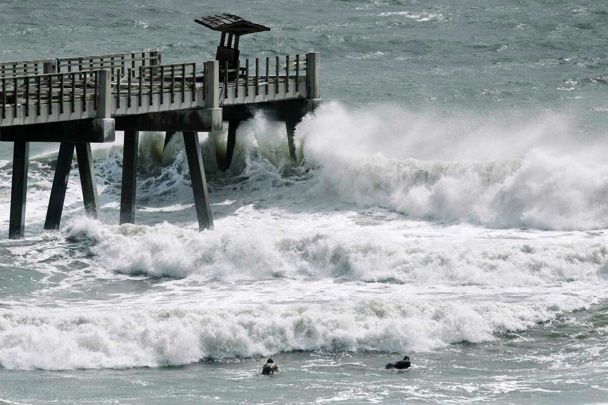A pair of surfers paddle out as incoming waves break at the end of the Jacksonville Beach Fishing Pier on Monday morning, Aug. 3, 2020, in Jacksonville, Fla., in waves generated by Isaias. (Bob Self/The Florida Times-Union via AP)