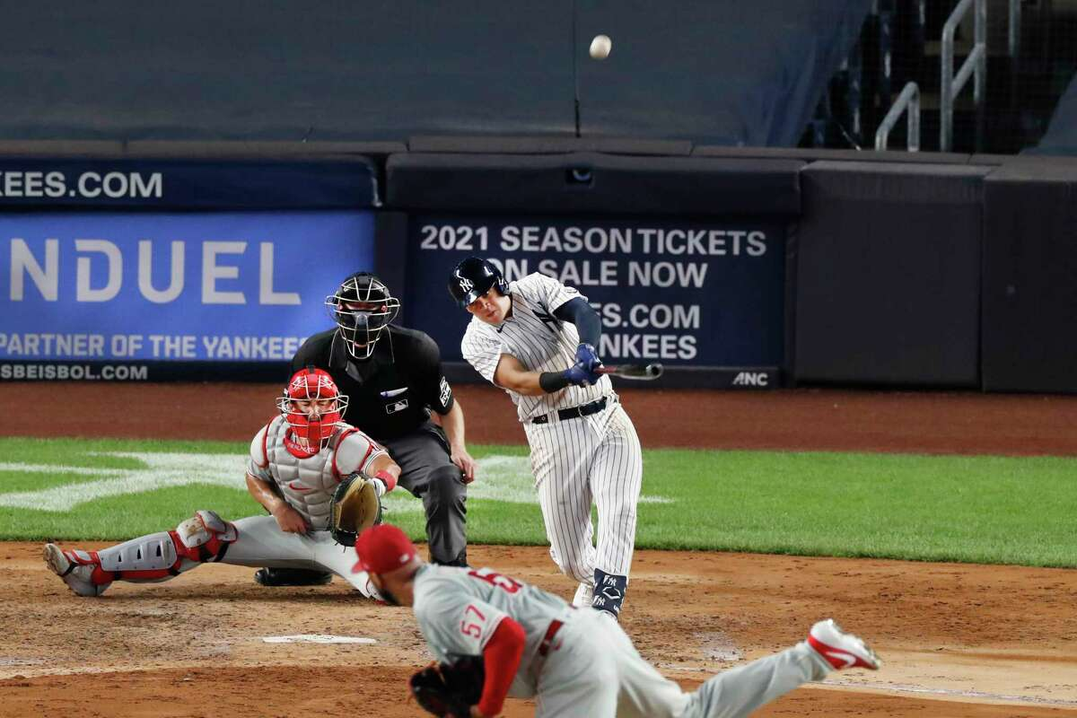 New York Yankees Gio Urshela hits a three-run, home run off Philadelphia Phillies relief pitcher Deolis Guerra (57) during the sixth inning of a baseball game, Monday, Aug. 3, 2020, at Yankee Stadium in New York. Philadelphia Phillies catcher J.T. Realmuto and home plate umpire Nic Lentz are behind the plate. (AP Photo/Kathy Willens)