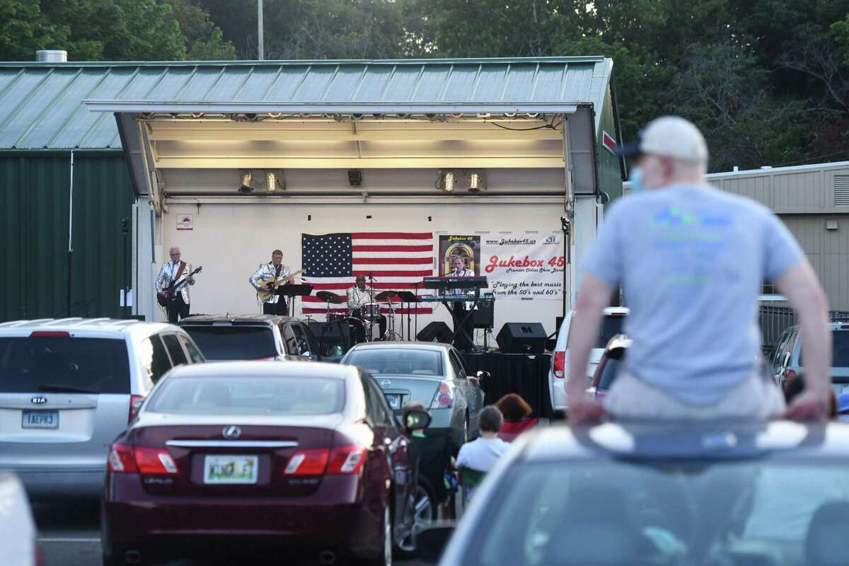 Folks watch the Jukebox 45 '50s and '60s cover band perform a socially distant concert at the Horseneck Lane parking lot in Greenwich, Conn. Wednesday, July 29, 2020. The performance was part of Greenwich Parks and Recreation's Summer