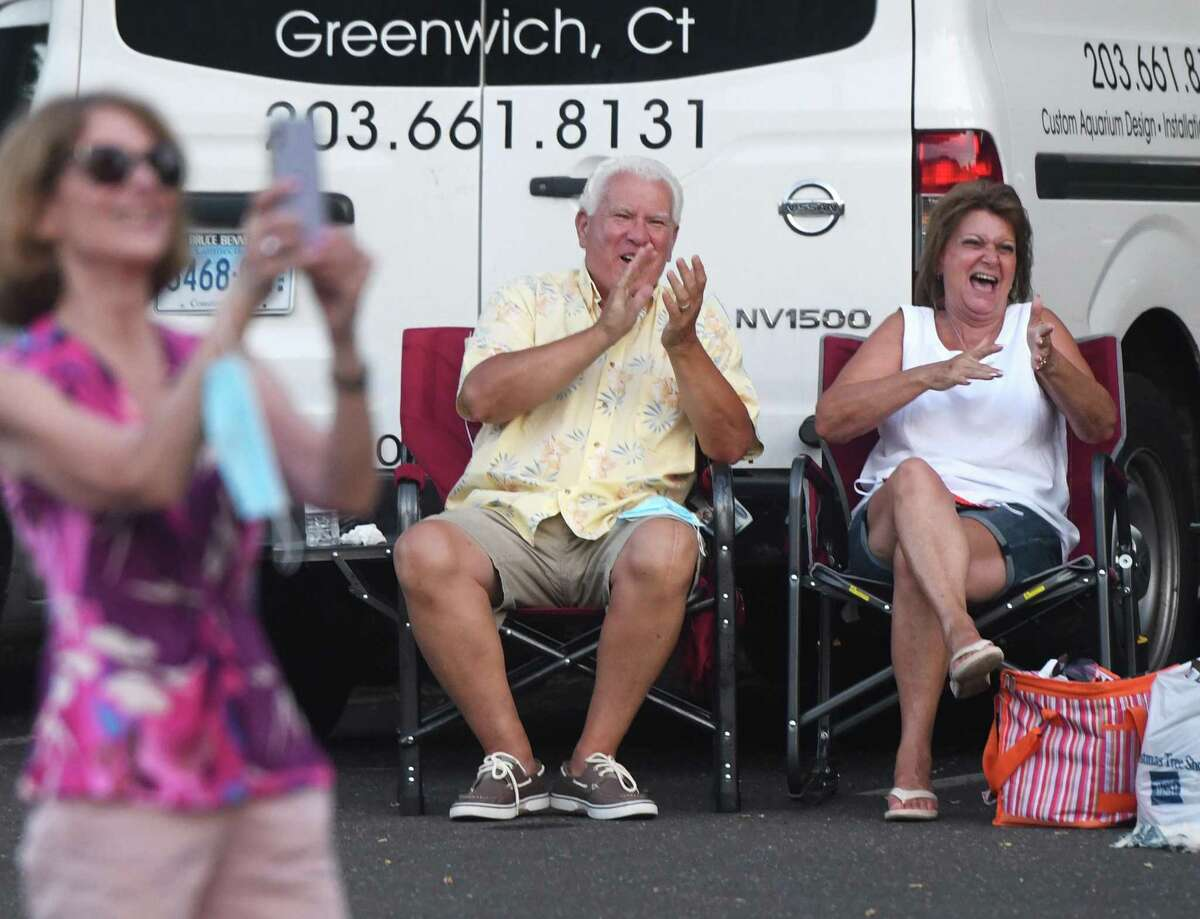 Ansonia's Dan and Beth Conti applaud the Jukebox 45 '50s and '60s cover band's socially distant concert at the Horseneck Lane parking lot in Greenwich, Conn. Wednesday, July 29, 2020. The performance was part of Greenwich Parks and Recreation's Summer