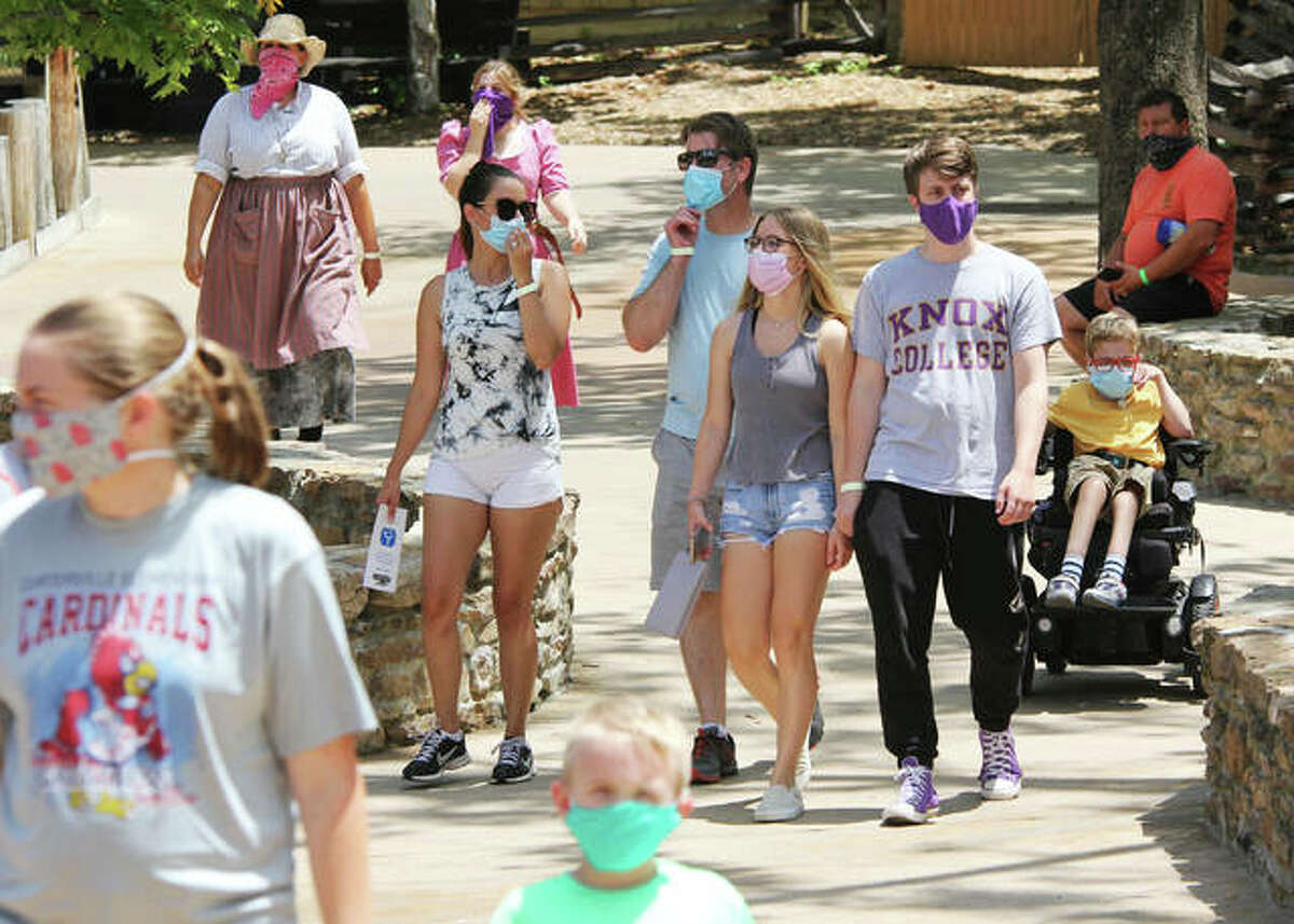 People wear masks while walking in Silver Dollar City, the 1880s-themed amusement park in Branson, Missouri. The park, like, similar venues opening back up, has a strict mask policy, as well as a number of other protocols in place because of COVID-19.