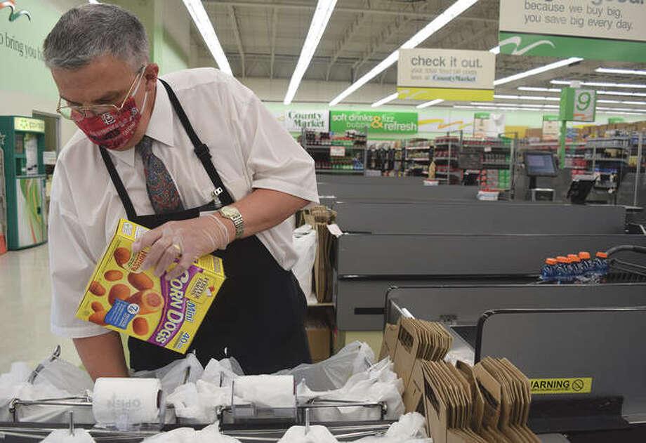 County Market employee Paul Baldwin bags groceries Monday for a customer. Photo: Samantha McDaniel-Ogletree   Journal-Courier