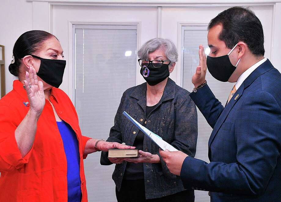 Webb County Democratic Party Secretary Ana Saenz, center, holds The Bible as Sylvia Bruni is sworn-in as the party chair by outgoing chair Albert Torres on Monday, Aug. 3. Photo: Cuate Santos / Laredo Morning Times / Laredo Morning Times