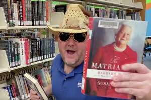 """Curbside Larry holds up """"The Matriarch,"""" a biography on the late First Lady and Houstonian Barbara Bush who championed literacy issues."""