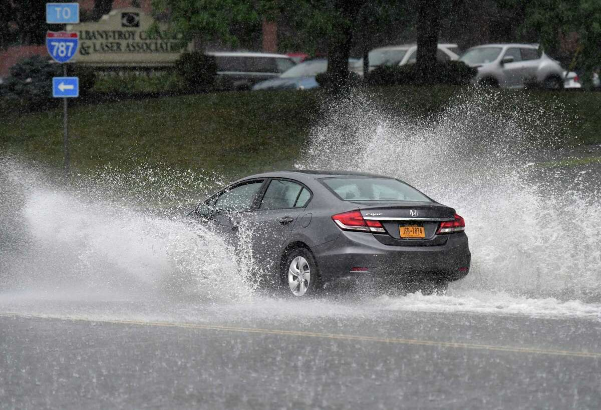 Rainwater is thrown from cars on Sixth Avenue as Tropical Storm Isaias pushes through the Capital Region on Tuesday, Aug. 4, 2020, in Troy, N.Y.