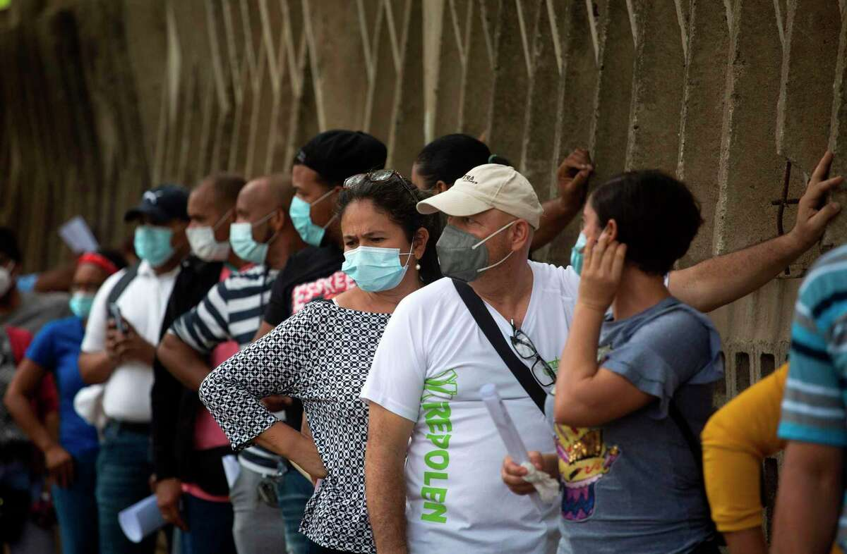 People wearing face masks line up to take a test that detects the novel coronavirus in Santo Domingo, Dominican Republic.